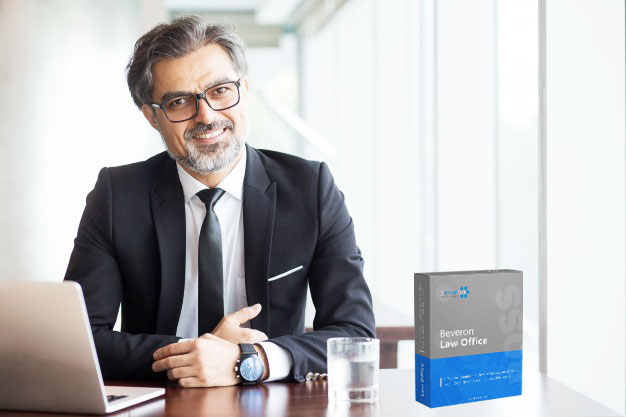 A man wearing black suit sitting in front of a laptop with Beveron law office case management software box